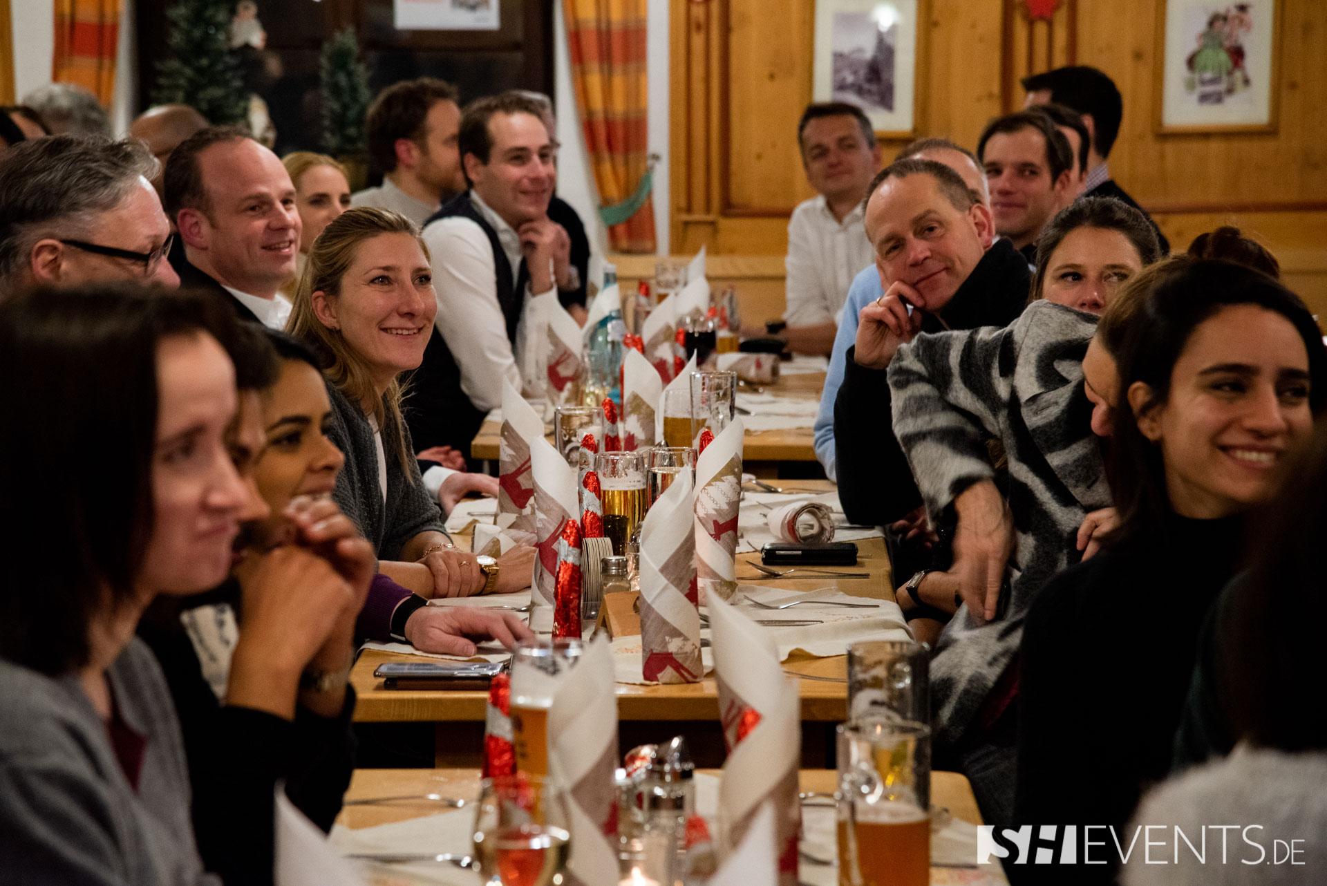 Gäste am Tisch lauschen einer Ansprache
