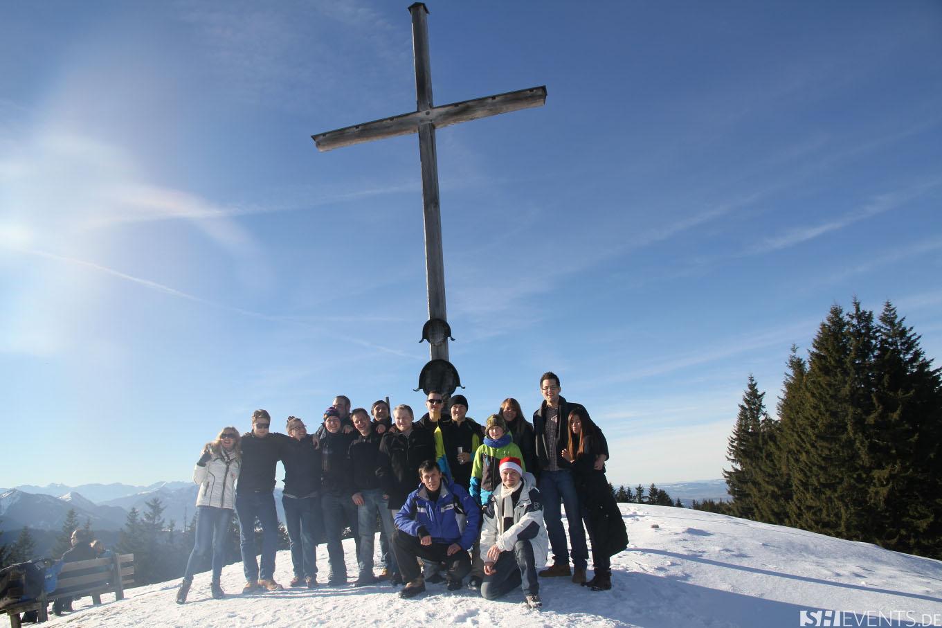 Gäste vor Gipfelkreuz im Schnee