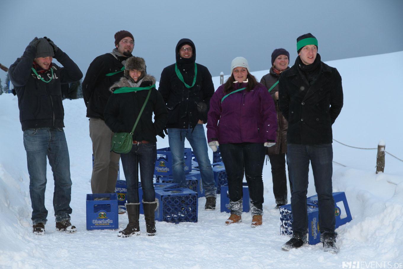 Gäste im Schnee beim Biertraglstapeln