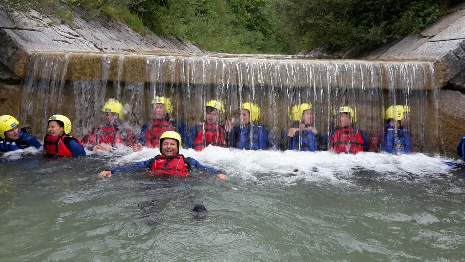 Männer unter Wasserfall beim Rafting