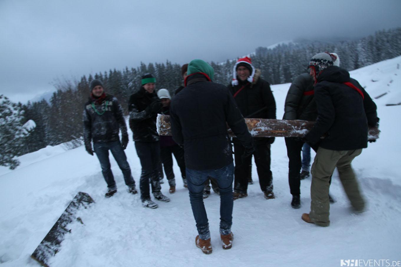 Gäste beim Baumstammweitwurf im Schnee
