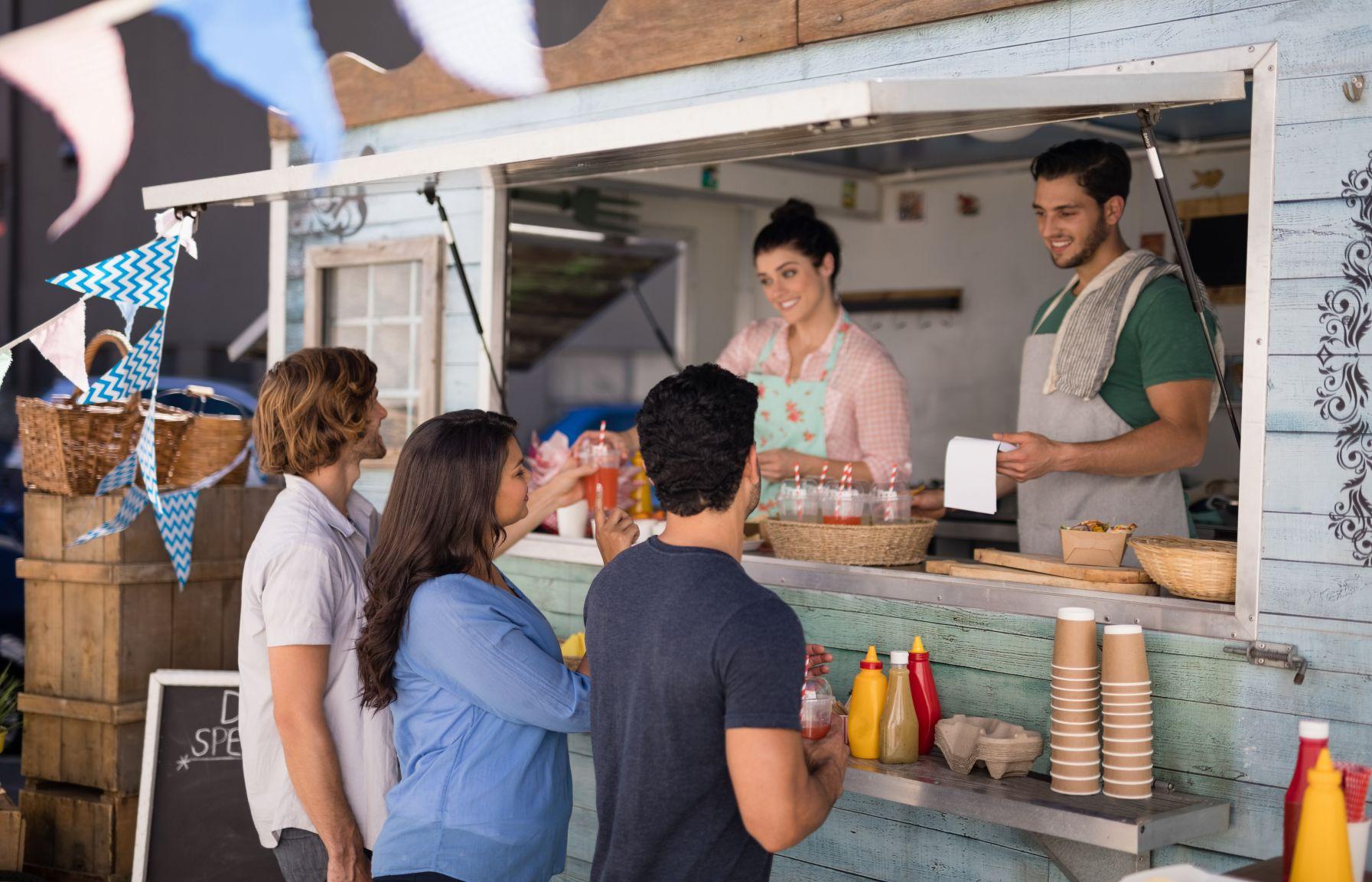 Menschen nehmen Essen von Foodtruck entgegen